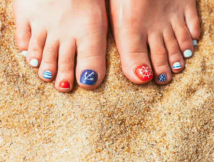 Bunte Fußnägel im Sand