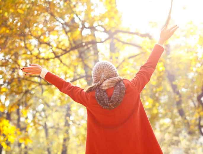 Frau im Wald mit Herbstlaub