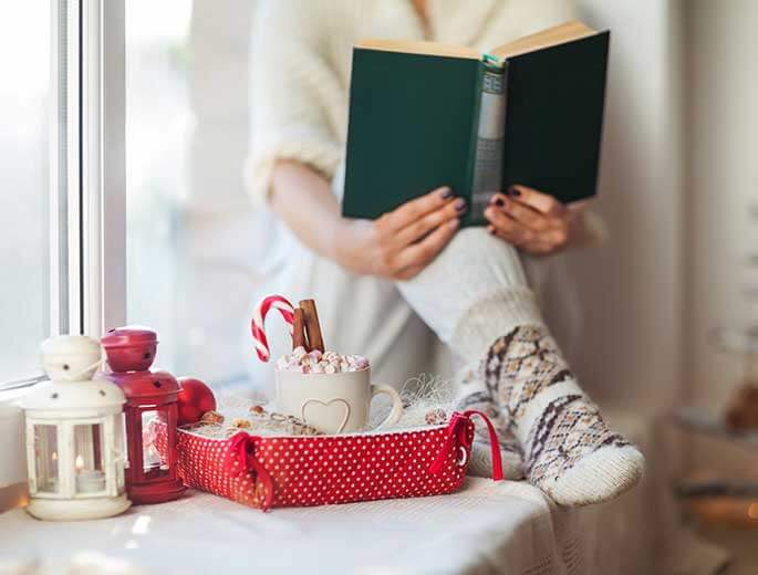 Buchverlosung Frau liest am Fenster