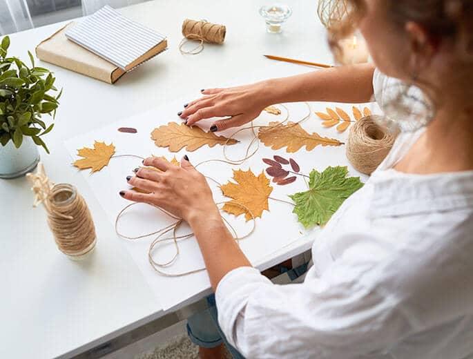 Herbstlaub bastelnde Frau
