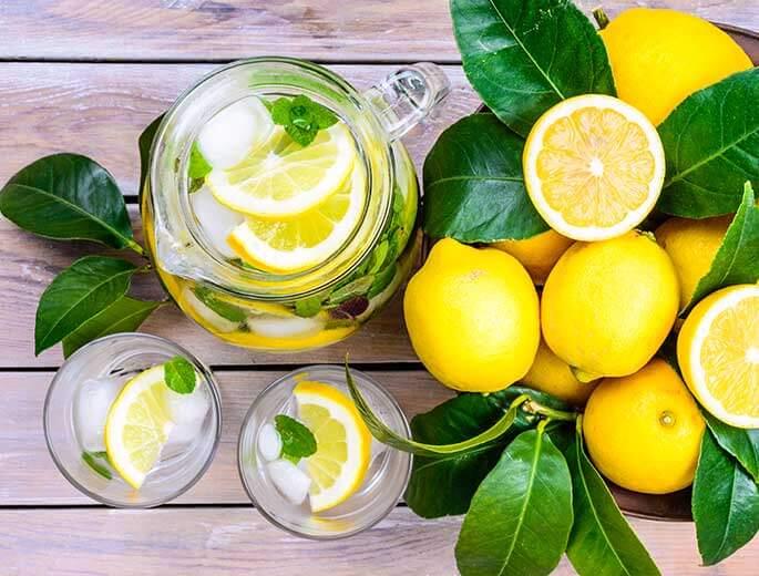 Zitronenwasser in Karaffe mit Zitronen