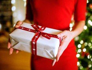 Festliches Styling Frau in rotem Kleid mit Geschenk in der Hand