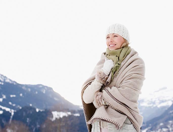 Schneekönigin Frau eingewickelt in Decke in den Bergen
