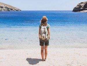Frau steht mit Rucksack am Strand