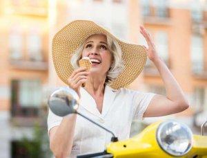 Frau mit Hut auf Motorroller
