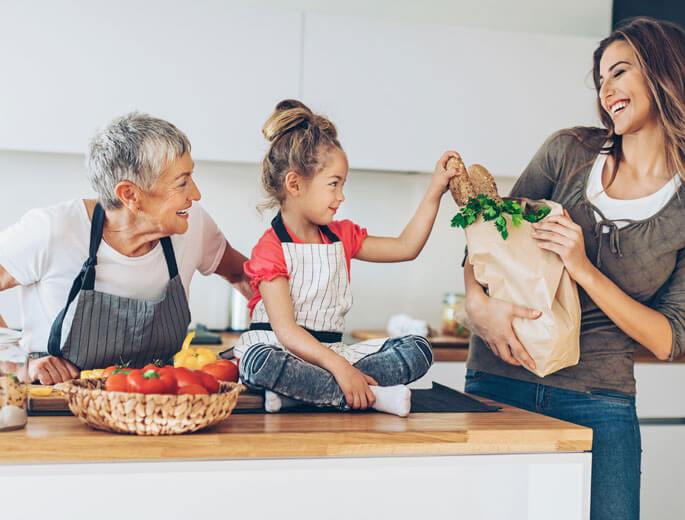 Großmutter und Enkelin kochen in Küche, Mutter mit Papiertüte, kein Müll