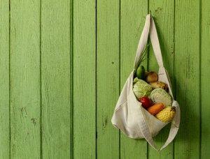 Stofftasche befüllt mit Gemüse hängt an grüner Wand, einkaufen mit Stofftasche, um Müll zu vermeiden