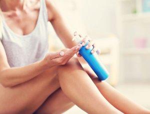 Frau cremt sich ihre Beine mit After Sun Lotion ein