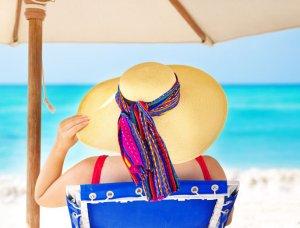Frau sitzt mit Sonnenhut unter Sonnenschirm am Strand