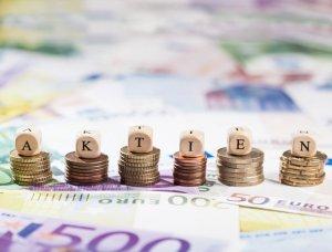 Würfel mit Aufschrift Aktien liegen auf Geldstapeln
