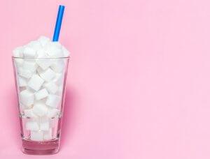 Zuckerwürfel im Glas mit Strohhalm vor rosa Hintergrund