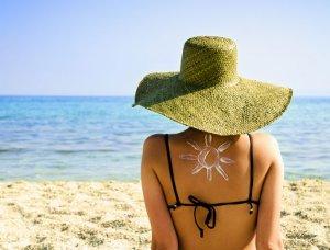Frau sitzt mit Sonnenhut am Strand mit Sonnencreme-Sonne auf dem Rücken