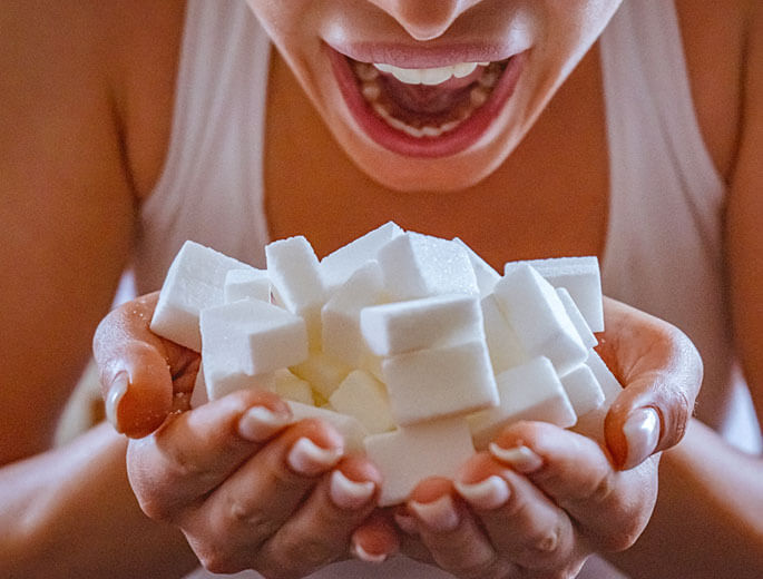 Frau hält viele Zuckerwürfel in den Händen, offener Mund