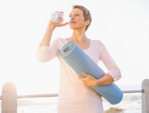 Frau trinkt Wasser mit Yogamatte