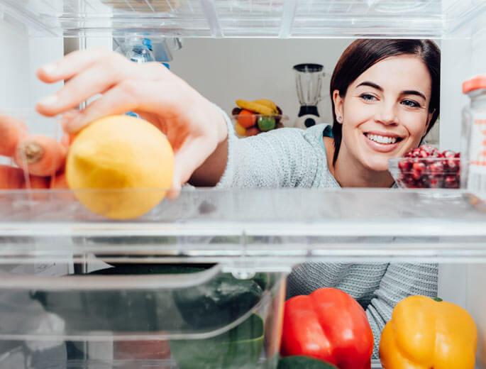 Frau räumt Lebensmittel in Kühlschrank