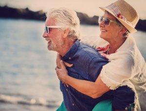 Älteres Paar Huckepack am Strand