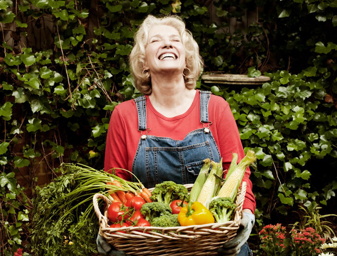 Lachende Frau hält Korb mit frischem Gemüse