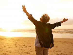 Dame mit offenen Armen am Strand